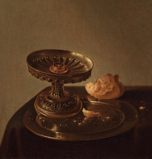 Jan Jansz. den Uyl - A still life of a silver tazza standing on a pewter plate, with pieces of bread, on a table covered with a dark cloth